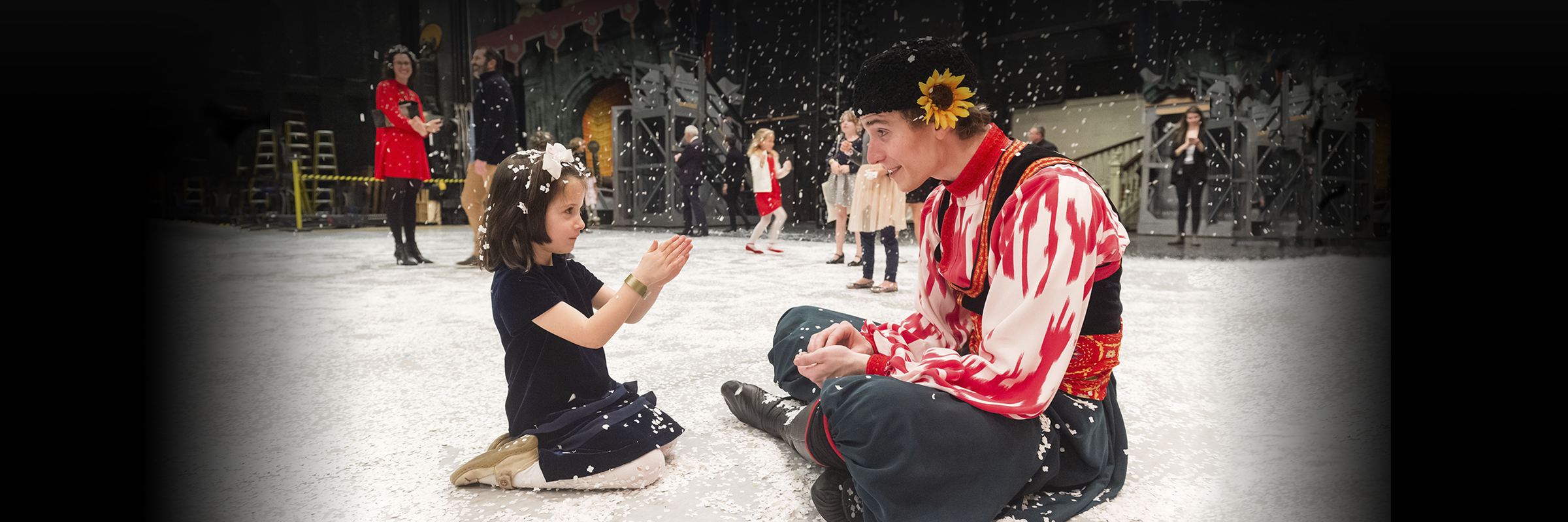 Dancer dressed as Cossack and child sitting on snow covered stage