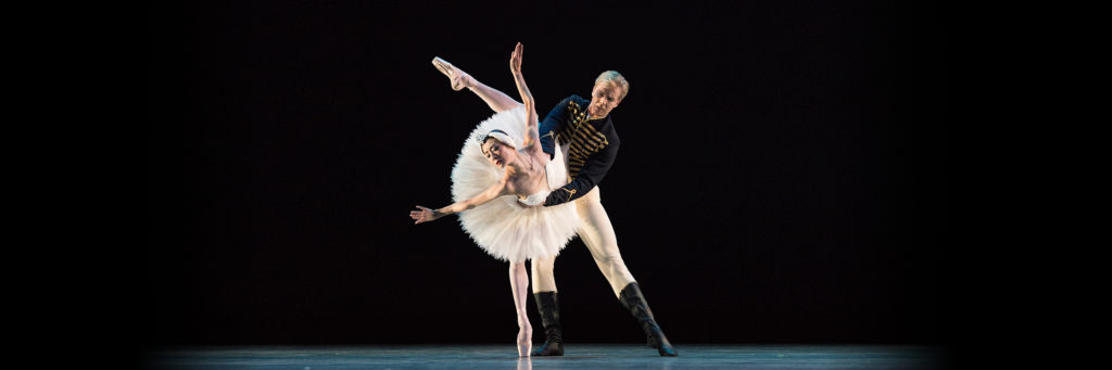 Siegfried supports Odette at the waist as she bends forward, balancing on her right leg, left leg bent aloft behind her, arms up