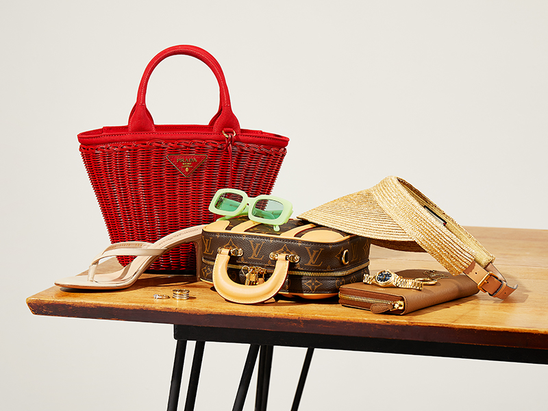 Handbags, sunglasses, jewelry, and shoes displayed on a table