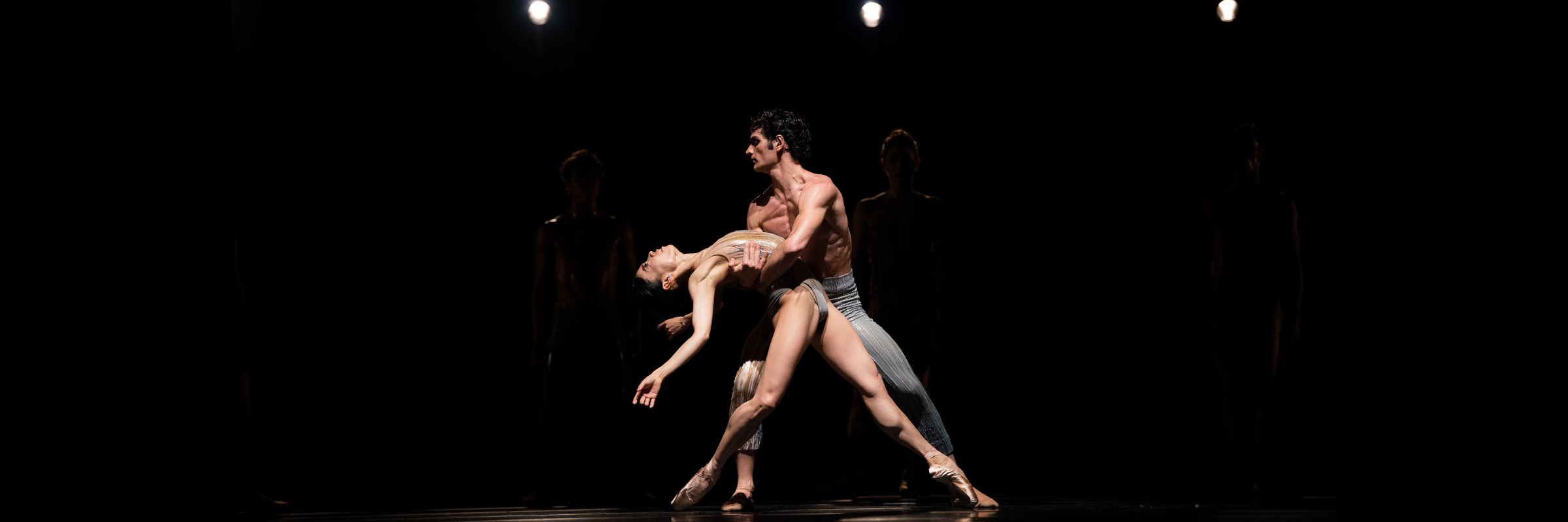 In a pool of light, a male dancer holds a female dancer in his arms as she arches her back, arms outstretched and feet pointed