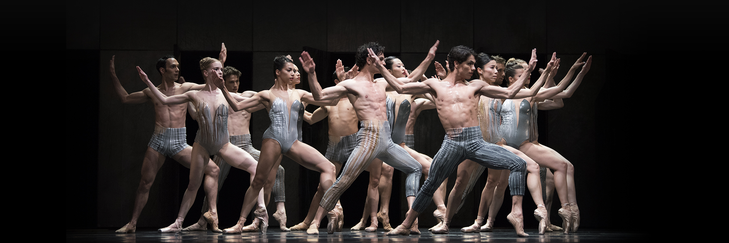 Seven male and seven female dancers lunge to their left, with left ankle raised, arms bent, hands raised, and palms out.
