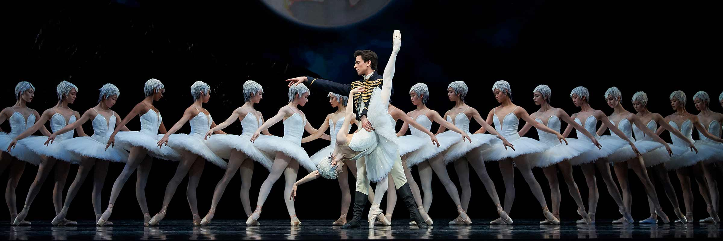 Before line of swans facing center, Siegfried faces right, holding Odette's waist as she bends over on right leg, left leg up