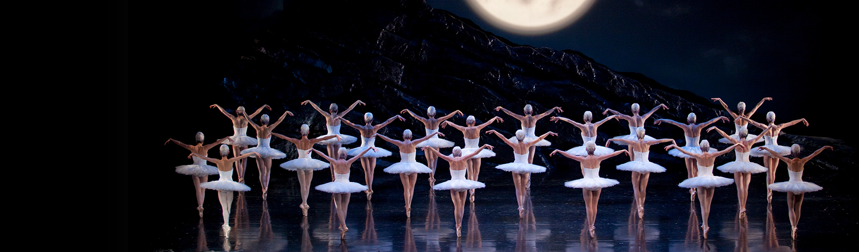 Three rows of swans—in white bodices, tutus, and skull caps—stand on pointe, facing a full moon silhouetting two flying swans
