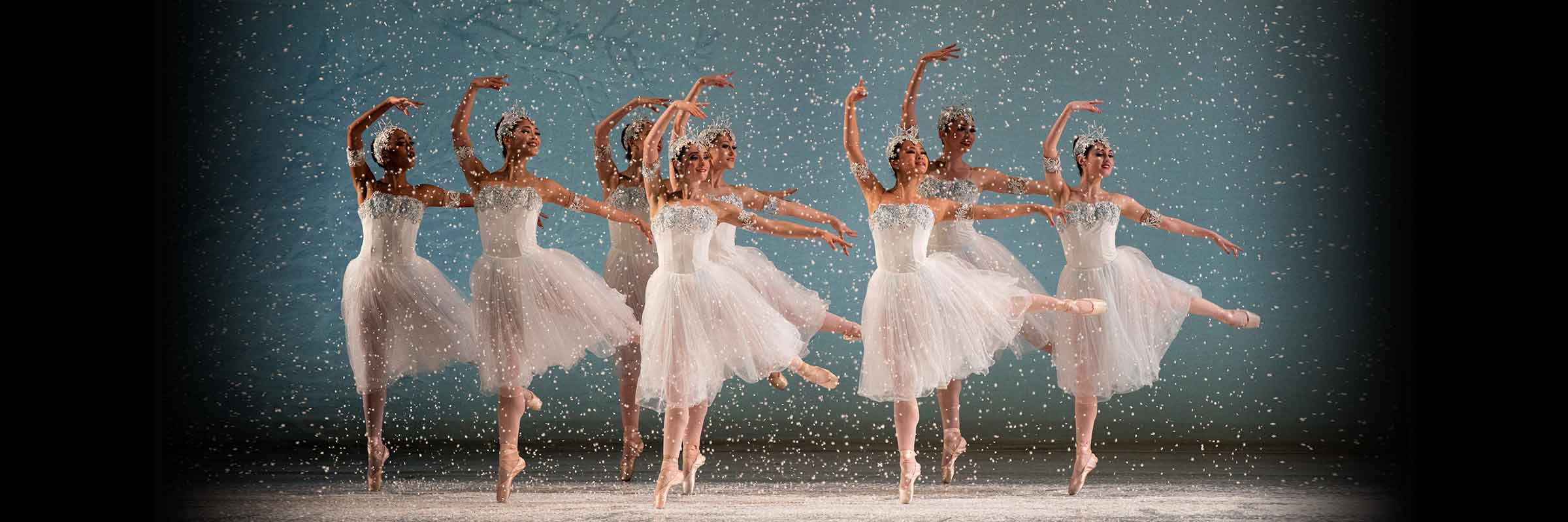 Snow falls as eight Snowflakes jump right, looking left, right legs down, left legs and arms out, right arms curved overhead